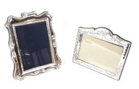 Two modern silver-mounted photograph frames including a landscape frame decorated in swags and bows,