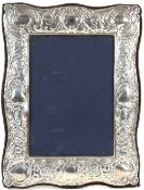 Modern silver-mounted frame, chased with scrolls and vacant cartouche, with velvet back and stand,