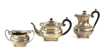 George V silver presentation three piece part tea service, comprising teapot, hot water jug and