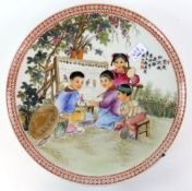 A Chinese famille rose circular dish, decorated with a scene of four children in a garden classroom;