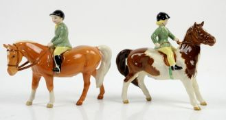 Pair of Beswick figures, a skewbald pony with girl rider and a Palomino with boy rider, each