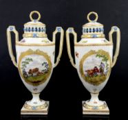 A pair of two handled Continental porcelain urns and covers with central cartouches painted with