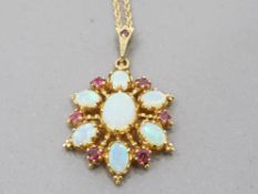A 9CT YELLOW GOLD OPAL AND RUBY PENDANT ON 9CT GOLD CHAIN 6.6G GROSS