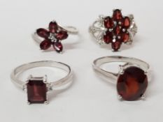 FOUR SILVER AND RED STONE RINGS STAMPED SIZES T T 1/2 AND U 16G GROSS