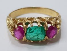 18CT YELLOW GOLD RUBY AND EMERALD THREE STONE RING COMPRISING OF A SINGLE EMERALD STONE IN THE