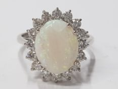 LADIES 18CT WHITE GOLD OPAL AND DIAMOND CLUSTER RING COMPRISING OF A SINGLE OVAL CUT, OPAL