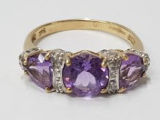 LADIES 9CT YELLOW GOLD PURPLE THREE STONE RING SET WITH A ROW OF ROUND CUT DIAMONDS BETWEEN EACH