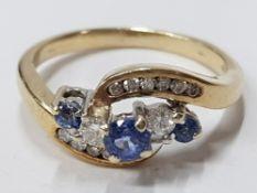 LADIES 18CT YELLOW GOLD TANZANITE AND DIAMOND TWIST CLUSTER RING COMPRISING OF THREE ROUND CUT