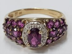 LADIES 9CT YELLOW GOLD PINK AND WHITE STONE CLUSTER RING COMPRISING OF AN OVAL PINK STONE SET IN A