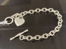 A SILVER LINK BRACELET WITH HEART SHAPED CHARM AND T BAR CLASP 21CM LONG 24.1G