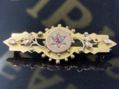 AN ANTIQUE 9CT YELLOW GOLD BROOCH WITH CENTRAL PINK STONE SURROUNDED BY SIX SEED PEARLS 3.8G GROSS