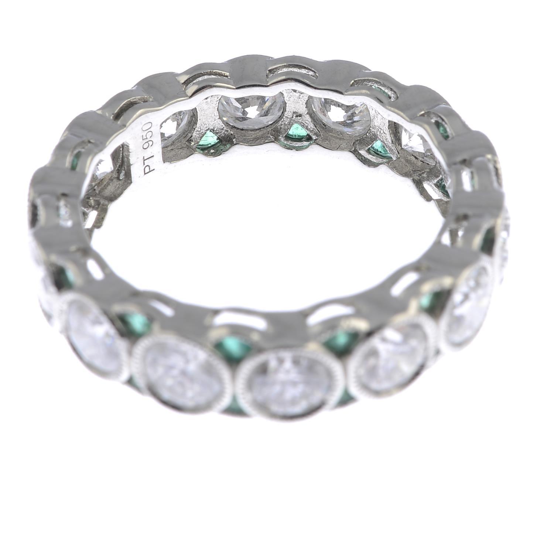 Lot 180 - A brilliant-cut diamond full eternity ring, with calibre-cut emerald spacers.