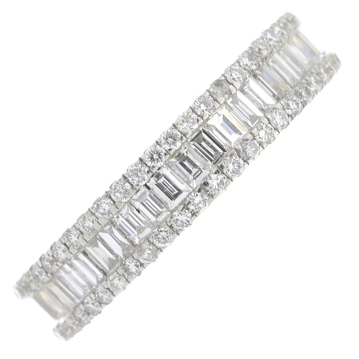 Lot 252 - An 18ct gold baguette and brilliant-cut diamond full circle eternity ring.Estimated total diamond