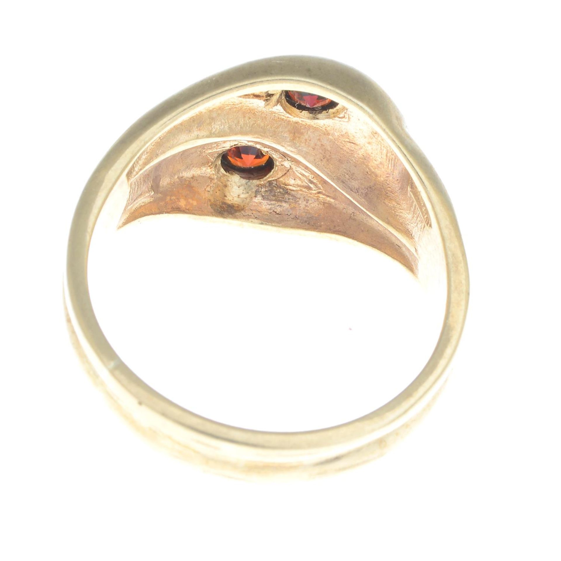 A 9ct gold snake ring, with red gem crest highlights.Hallmarks for 9ct gold. - Bild 2 aus 3
