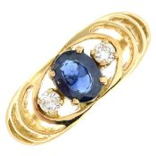 A sapphire and diamond three-stone ring.Estimated total diamond weight 0.10ct.Stamped 18.Ring size