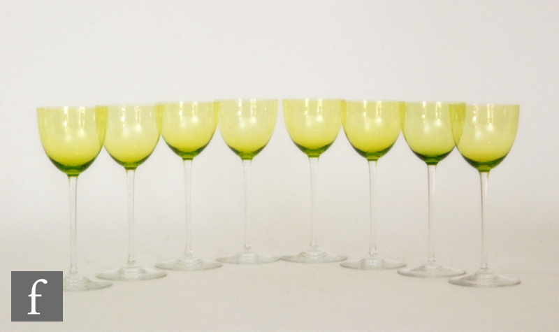 A set of eight 20th Century Baccarat wine glasses with a plain lime green bowl raised to a slender