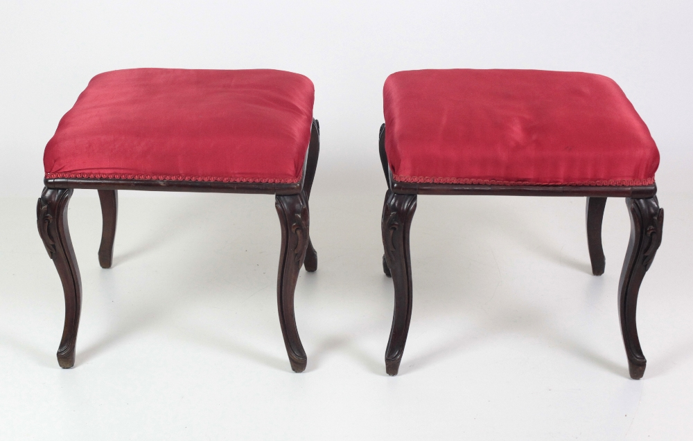 Lot 21 - An attractive pair of Victorian Foot Stools, covered in red silk material on carved cabriole legs.
