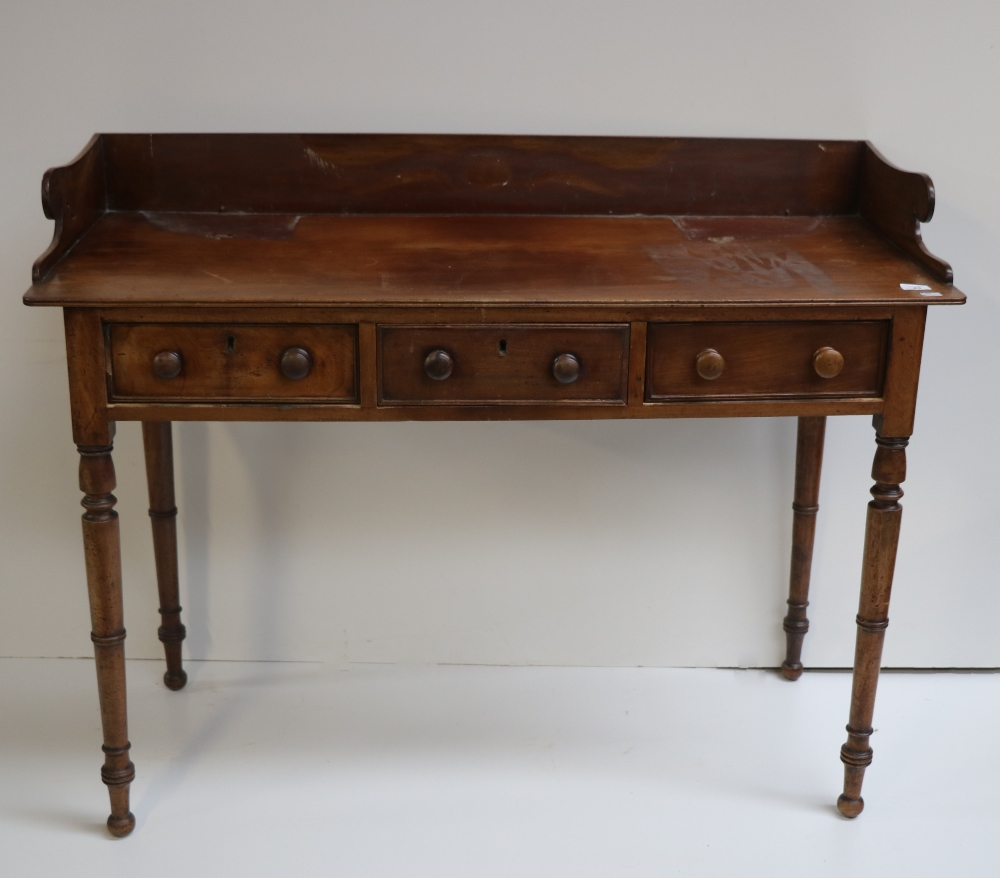 Lot 45 - A late Georgian mahogany Dressing Table, with shaped back over three frieze drawers on turned legs.