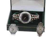 White metal lady's bangle watch, black enamel dial with Arabic numerals, minute track and five