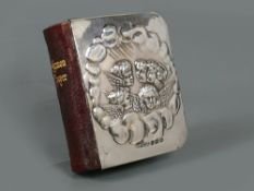 Miniature Edwardian silver front Book of Common Prayer embossed with angels amongst clouds,