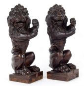 Pair of carved oak lions, each modelled on hind legs as if to hold a banner or flag upon on square
