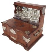 Oak three bottle tantalus with silver plated mounts, the mirror back over a divided compartment