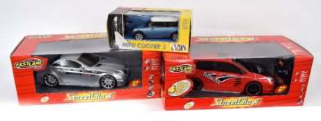 Two Fastlane 'Street Glow' remote control cars, a Honda and a Mercedez; together with a smaller Mini