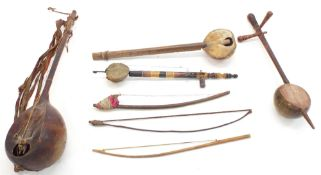 Four various antique and later African and other folk fiddles; together with three various folk