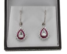 Superb pair of white gold ruby and diamond drop earrings, each with central pear shaped old-cut