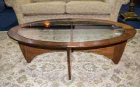G Plan Teak Oval Shaped Coffee Table with glass top supported on a shaped base.