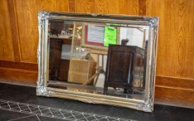 A Modern Gilt Framed Bevelled Mirror broad swept frame. Measures 29 by 42 inches.