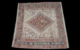 A Turkish Woven Wool Carpet with beige ground and traditional Middle Eastern red border detail