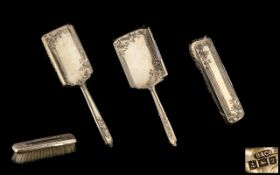 A Three Piece Silver Backed Vanity Set comprises two brushes and mirror.