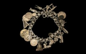 A Vintage Good Quality Silver Fancy Link Bracelet with over 20 charms plus silver coins.