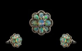 Opal Cluster Ring, comprising eight oval cut cabochons of opal with a generous display of colours,