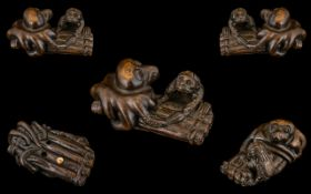 A Japanese Boxwood Netsuke Carving of a Kappa astride a raft with an octupus.
