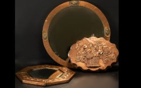 An Octagonal Beaten Copper Arts and Crafts Wall Mirror with embossed decoration. The diameter 15.