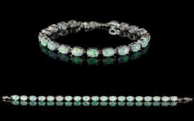 A Contemporary Silver And Opal Set Tennis Bracelet - Comprising 19 Oval Cabochon Opals.