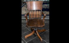 An American Golden Oak Office Swivel Chair of an unusual splat back on a cruciform base.