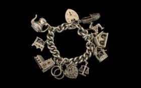 A Sterling Silver Charm Bracelet Loaded with 11 Good Quality Old Charms.