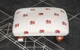Small Footstool raised on four ball feet and upholstered in beige with red elephant print.
