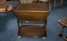 An Ercol Elm Tea Trolley with flat sides on castor feet. The trolley measuring 18 inches wide by