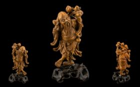 Chinese Boxwood Carved Figure of a Deity holding a branch of peaches on a hardwood base.