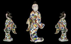 Japanese Antique Imari-Style Figure of a courtesan wearing a flowing gown, holding a fan in one