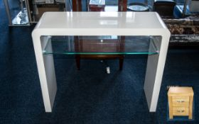 A Contemporary White High Gloss and Glass Console Table. 30 inches in height and 35 inches wide.