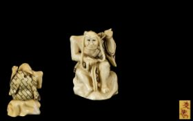 An Antique Japanese Ivory Netsuke of an Old Man with Long Eye Brows sitting on a rock.