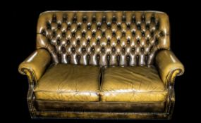Leather Two Seater Chesterfield Sofa in brown colour, with rolling arms and two loose seat cushions.