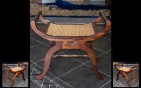 Piano Stool/Seat in mahogany with rattan seat. Curved wood base raised on four legs with stretcher.