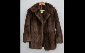 Ladies Fur Jacket. Collar and reveres, two slit pockets, half belt to back. Fully lined in brown