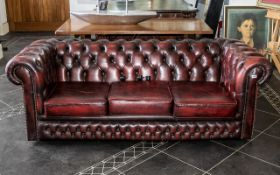 Three Seater Chesterfield Sofa, covered in a burgundy leather and supported on castors.